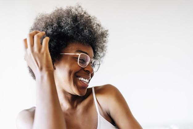 흰 벽에 포즈를 취하는 쾌활한 아프리카계 미국인 여성