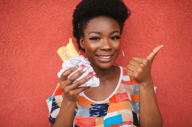Cheerful african american girl with burger in her hand shows thumb up gesture over red wall