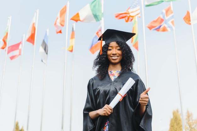 Веселый афро-американский аспирант с дипломом в руке