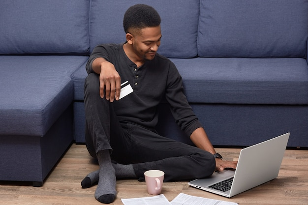 Cheerful african american guy holds credit card, checks her bank account on laptop computer, makes online shopping, chooses item from webstore, poses at floor in cozy room, drinks hot coffee