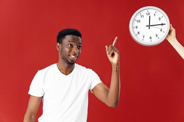 白いtシャツの陽気なアフリカ系アメリカ人は、時計の孤立した背景で指を示しています