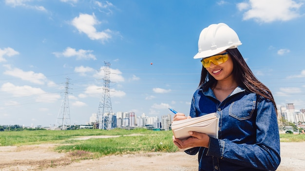 Cheerful african american lady in safety helmet taking notes near high voltage line