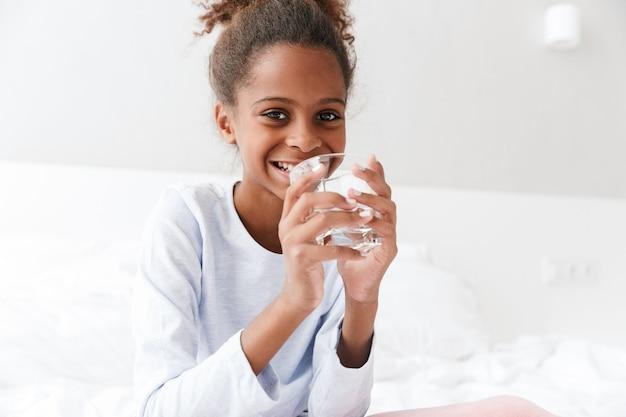 Веселая афроамериканская маленькая девочка пьет воду из стакана, сидя в постели у себя дома