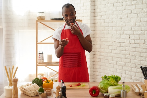 Cheerful african american man in apron eats tomatoes.
