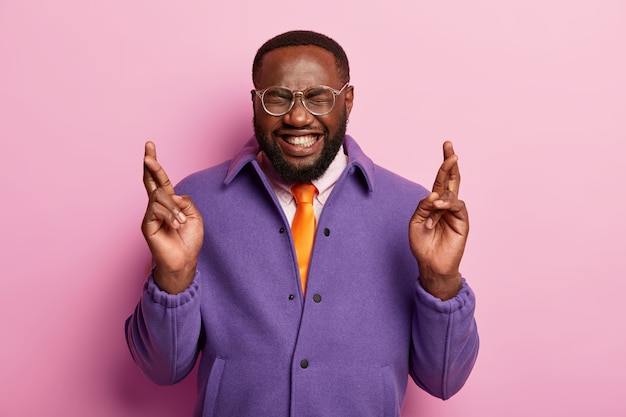 쾌활한 아프리카 계 미국인 남자는 중요한 사건 전에 손가락을 교차하고 행운을 바라며 큰 소원을 가지고 투명 안경을 착용합니다.