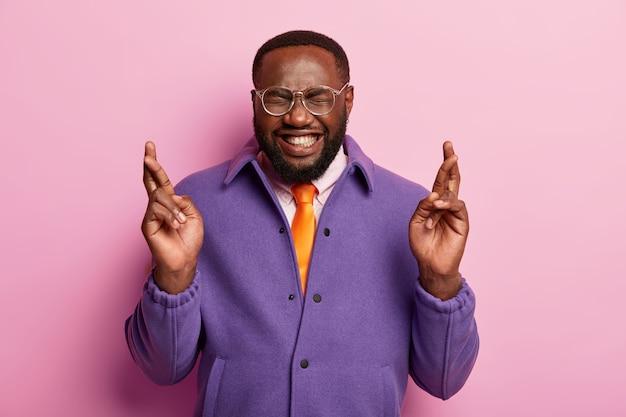 Allegro uomo afroamericano incrocia le dita prima di un evento importante, spera in buona fortuna, ha grandi desideri, indossa occhiali trasparenti