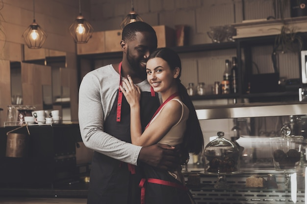Cheerful african american man hugs beautiful girl