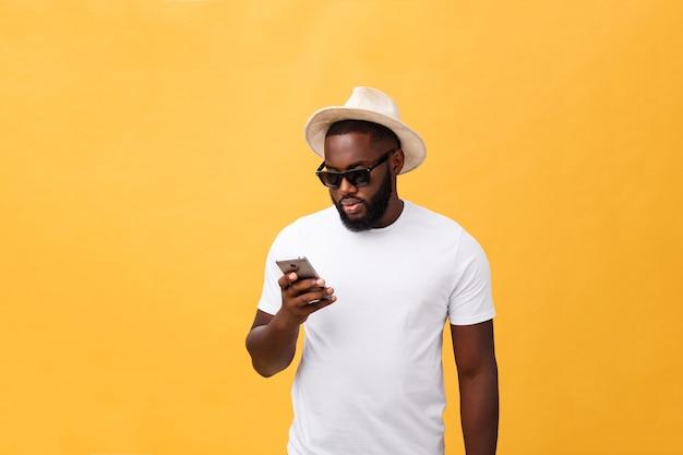 Веселый афро-американский мужчина в белой рубашке с помощью приложения для мобильного телефона.