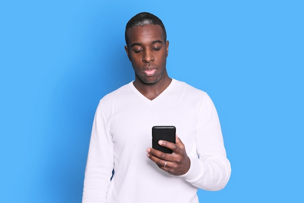 Cheerful african american man in white sweater using mobile phone application.
