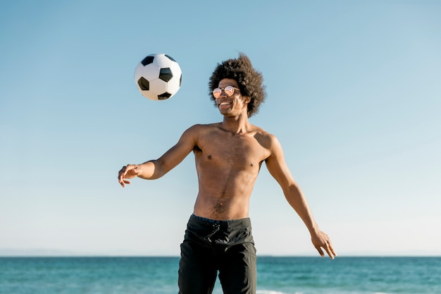Cheerful african american sportsman playing football on seaside