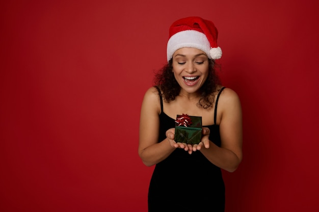 쾌활한 아프리카계 미국인 여성이 손에 든 작고 아름다운 크리스마스 선물 상자를 보고 행복감을 느끼고 있으며, 광고를 위한 복사 공간이 있는 빨간색 배경 위에 격리되어 있습니다. 새 해와 메리 크리스마스 개념입니다.