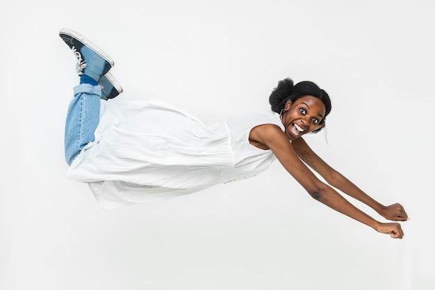 飛んでいるポーズで陽気なアフリカ系アメリカ人の女性