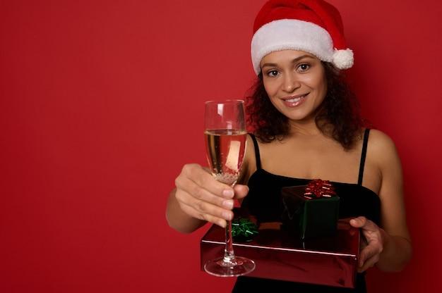 아름다운 이빨 미소를 가진 쾌활한 아프리카계 미국인 여성은 반짝이는 빨간색 녹색 선물 종이로 싸인 크리스마스 선물 상자를 들고 카메라에 스파클링 와인과 샴페인 플루트를 보여줍니다. 복사 공간