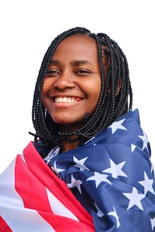 Cheerful african american woman wrapped in usa flag looking away on a white background.