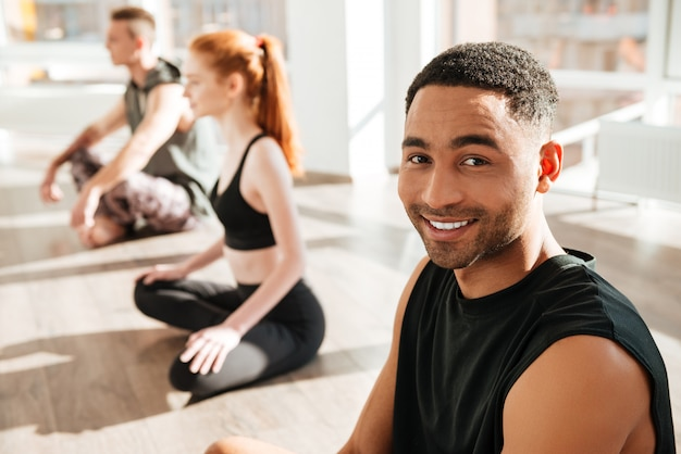 Cheerful african american young man practicing yoga in group