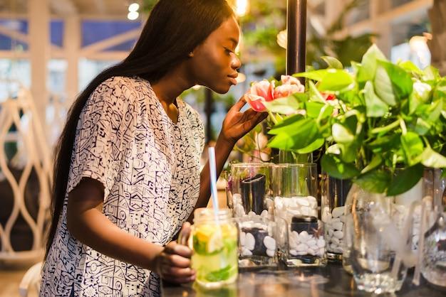 カフェで夏のドレスを着た陽気なアフリカ系アメリカ人の若い女性は、花瓶の白い花を嗅ぎます。