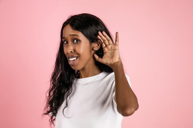 Веселая афроамериканская молодая женщина, изолированная на коралловом пространстве, эмоциональная и выразительная
