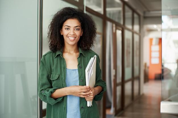 Жизнерадостный африканский красивый студент женщины усмехаясь держащ книги в университете. концепция образования
