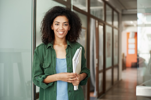 Cheerful african beautiful woman student smiling holding books in university. education concept.