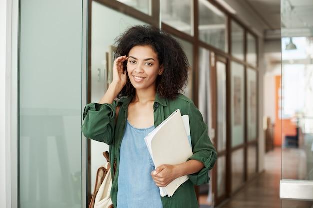 Волосы жизнерадостного африканского красивого студента женщины усмехаясь касающие держа книги в университете. концепция образования