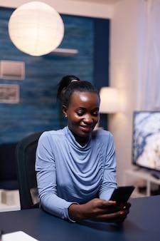 リモートで作業しているホームオフィスで夜遅くにスマートフォンで陽気なアフリカのビジネス女性のテキストメッセージ。残業をしている最新技術のネットワークワイヤレスを使用している従業員。