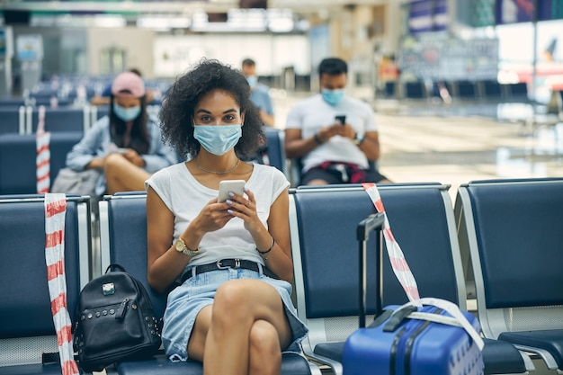 Cheerful african female wearing protective mask sitting in the bench in lounge zone of airport