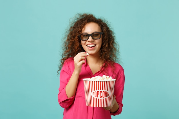Cheerful african girl in 3d imax glasses watching movie film and holding popcorn isolated on blue turquoise wall background in studio. people emotions in cinema, lifestyle concept. mock up copy space.