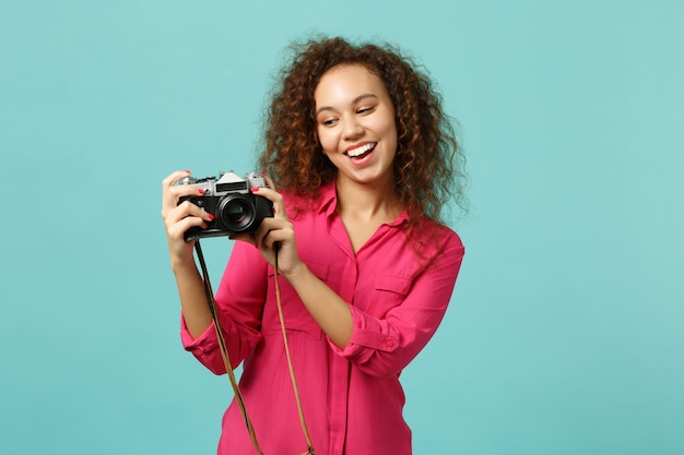 Cheerful african girl in casual clothes take pictures on retro vintage photo camera isolated on blue turquoise wall background in studio. people sincere emotions lifestyle concept. mock up copy space.