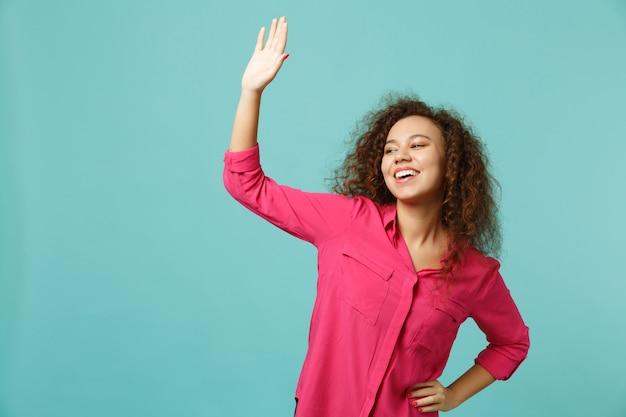 Allegra ragazza africana in abiti casual agitando e salutando con la mano mentre nota qualcuno isolato su sfondo blu turchese in studio. concetto di stile di vita di emozioni sincere della gente. mock up copia spazio.