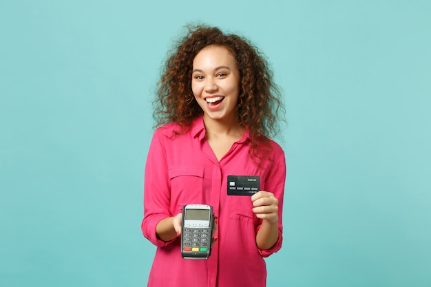 Cheerful african girl hold wireless modern bank payment terminal to process, acquire credit card payments isolated on blue turquoise background. people emotions, lifestyle concept. mock up copy space.
