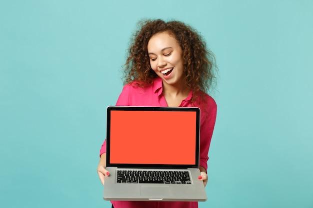 カジュアルな服装で陽気なアフリカの女の子は、スタジオで青いターコイズブルーの背景に分離された空白の空の画面でラップトップpcコンピューターを保持します。人々の誠実な感情、ライフスタイルのコンセプト。コピースペースをモックアップします。