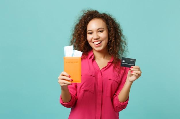 평상복을 입은 쾌활한 아프리카 소녀는 파란색 청록색 벽 배경에 격리된 여권, 탑승권, 신용 은행 카드를 들고 있습니다. 사람들은 진심 어린 감정 라이프 스타일 개념입니다. 복사 공간을 비웃습니다.