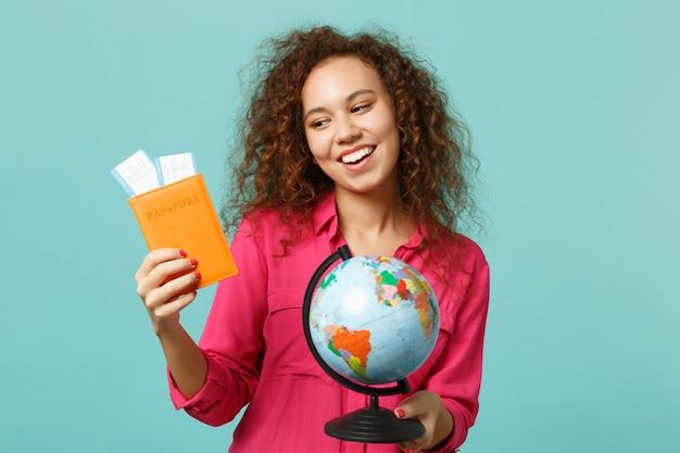 地球の世界の地球、パスポート搭乗券、青いターコイズブルーの背景で隔離のカジュアルな服を着た陽気なアフリカの女の子。人々の誠実な感情、ライフスタイルのコンセプト。コピースペースをモックアップします。
