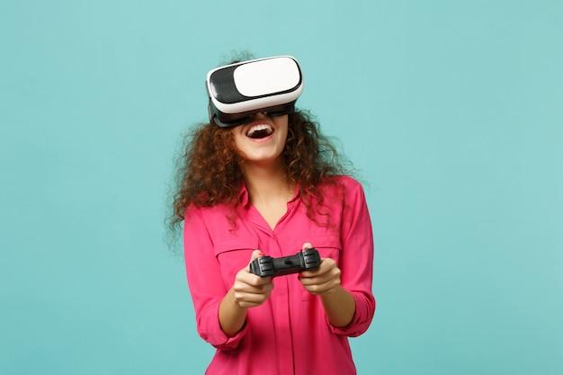 Веселая африканская девушка в повседневной одежде смотрит в гарнитуру, играя в видеоигры с джойстиком, изолированным на синем бирюзовом стенном фоне. люди искренние эмоции, концепция образа жизни. копируйте пространство для копирования.