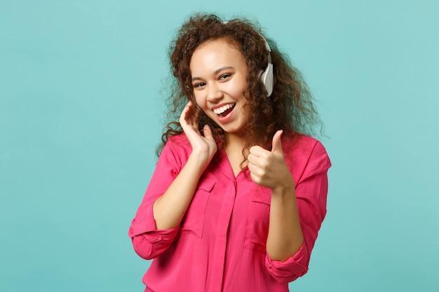 スタジオで青いターコイズブルーの背景に分離されたヘッドフォンで音楽を聞いて親指を示すカジュアルな服を着た陽気なアフリカの女の子。人々の誠実な感情のライフスタイルの概念。コピースペースをモックアップします。
