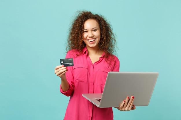 ラップトップpcコンピューターを使用してカジュアルな服装で陽気なアフリカの女の子は、スタジオで青いターコイズブルーの背景に分離されたクレジット銀行カードを保持します。人々の誠実な感情のライフスタイルの概念。コピースペースをモックアップします。