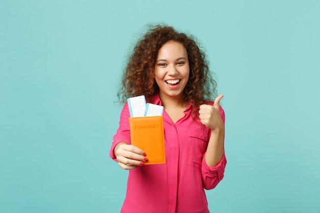 분홍색 캐주얼 옷을 입은 쾌활한 아프리카 소녀는 엄지손가락을 치켜들고, 여권을 들고, 파란색 청록색 배경에 격리된 탑승권을 보여줍니다. 사람들은 진심 어린 감정 라이프 스타일 개념입니다. 복사 공간을 비웃습니다.