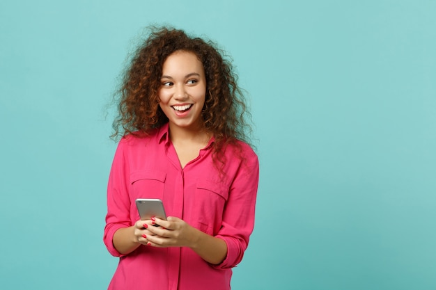 스튜디오의 파란색 청록색 벽 배경에 격리된 휴대폰 입력 sms 메시지를 사용하여 분홍색 캐주얼 옷을 입은 쾌활한 아프리카 소녀. 사람들은 진심 어린 감정, 라이프 스타일 개념입니다. 복사 공간을 비웃습니다.