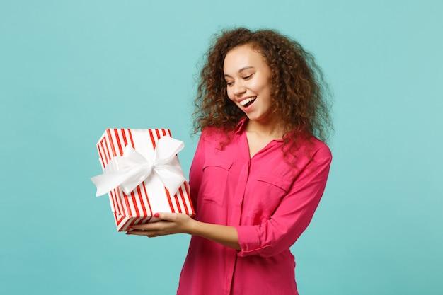 ピンクの服を着た陽気なアフリカの女の子は、青いターコイズブルーの壁の背景に分離されたギフトリボンと赤い縞模様のプレゼントボックスを保持します。国際女性の日の誕生日の休日の概念。コピースペースをモックアップします。