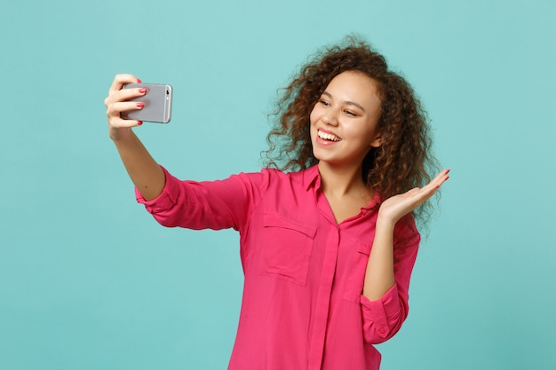 Cheerful african girl in pink casual clothes doing selfie shot on mobile phone isolated on blue turquoise wall background in studio. people sincere emotions, lifestyle concept. mock up copy space.