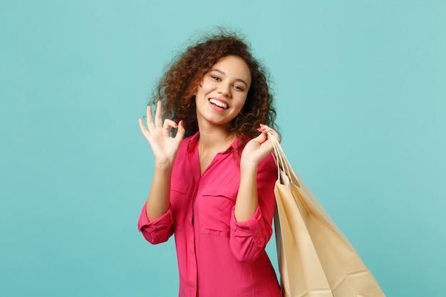 파란색 청록색 벽 배경에서 쇼핑한 후 구매한 패키지 가방을 들고 ok 제스처를 보여주는 쾌활한 아프리카 소녀. 사람들은 진심 어린 감정 라이프 스타일 개념입니다. 복사 공간을 비웃습니다.