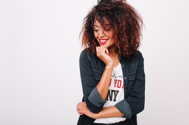 Allegra ragazza africana con trucco luminoso in posa con un sorriso timido e distoglie lo sguardo davanti al muro bianco. ritratto dell'interno di signora carina con pelle marrone chiaro che si diverte e ride.