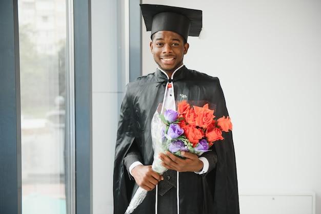 Веселый африканский выпускник мужского пола с дипломом