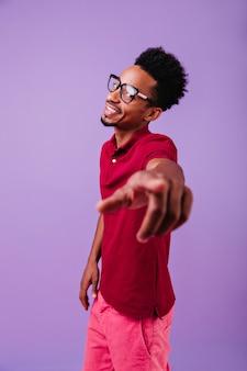 손가락을 가리키는 안경에 쾌활 한 아프리카 남성 모델입니다. 즐기는 잘 생긴 똑똑한 남자.