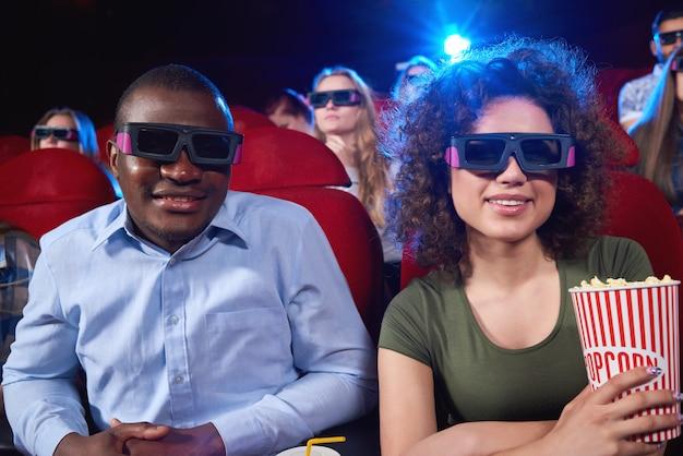 陽気なアフリカ人と3 dメガネをかけて彼のガールフレンドがポップコーンを押しながら映画を楽しみながら一緒に映画を楽しんでいるカップルは、ロマンスの友人の友情レジャーエンターテイメントとデートしています。