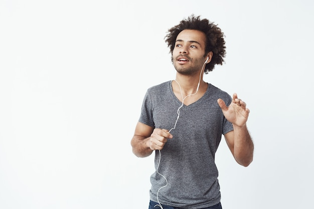 Cheerful african man listening to music in headphones dancing singing.
