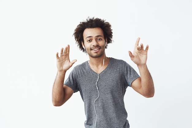 Cheerful african man listening to music in headphones dancing singing.
