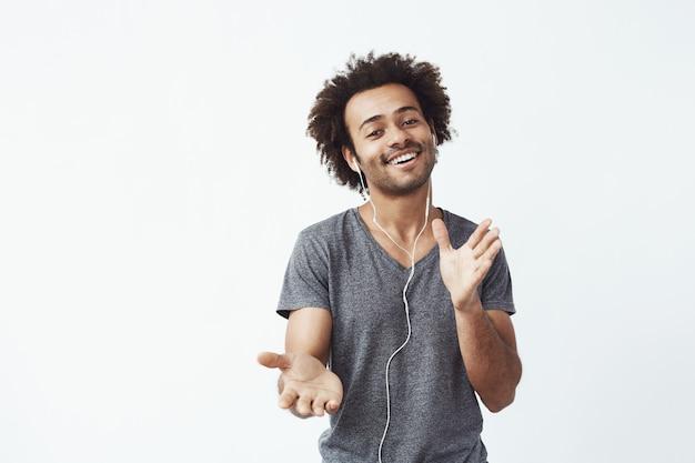 Жизнерадостный африканский человек слушая к музыке в наушниках танцуя петь.