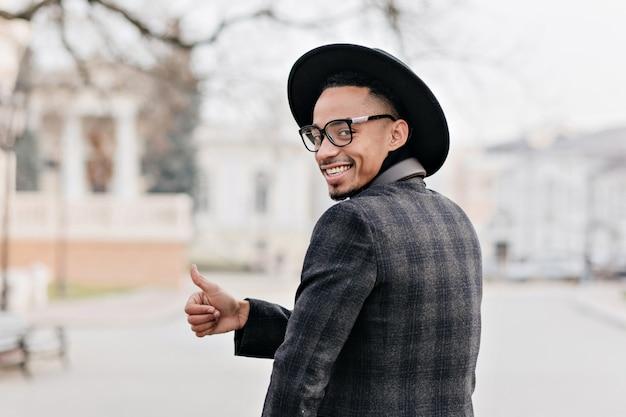 肩越しに見ている陽気なアフリカ人。笑顔で親指を示すエレガントなジャケットの面白い黒人の男。