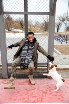 Cheerful african man playing with dog and laughing outdoors